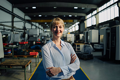 Portrait of a smiling businesswoman in a factory - p300m2170455 by Kniel Synnatzschke