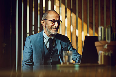 Senior businessman sitting in sustainable office, using laptop - p300m2170460 by Maya Claussen
