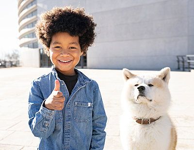Smiling boy gesturing thumbs up while standing by dog sitting on footpath - p300m2252376 by Jose Carlos Ichiro