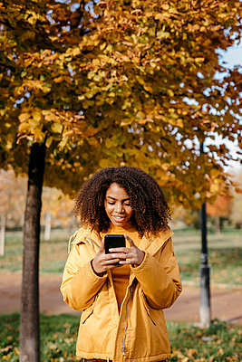 Young Afro woman using smart phone while standing in park during autumn - p300m2267516 by Tania Cervián