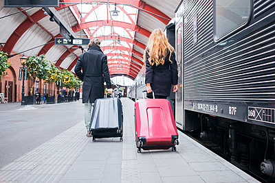 Couple pulling suitcases on train station - p312m2174538 by Viktor Holm