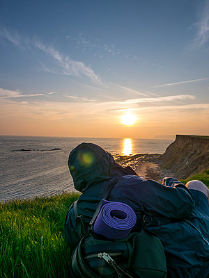 Backpacker  Sitting on Cliff Admiring Ocean View at Sunset - p669m1443205 by David Harrigan