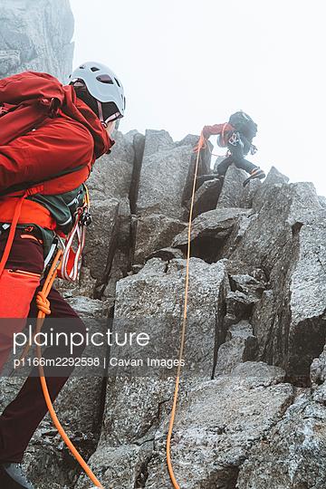 High Alpine mountain guide ascending granite ridge near Mont Blanc - p1166m2292598 by Cavan Images