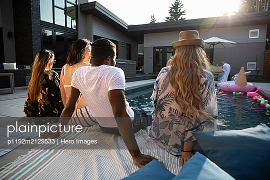 Young adult friends relaxing at sunny, summer poolside - p1192m2129533 by Hero Images