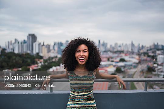 Panama, Panama City, portrait of laughing young woman on balcony - p300m2080943 by Kike Arnaiz
