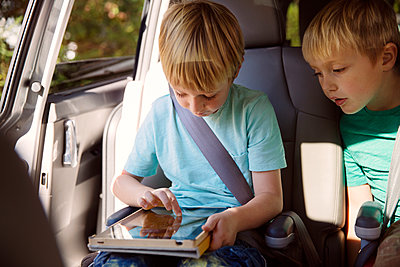 Boy using tablet computer while sitting in car - p1166m1096491f by Cavan Images