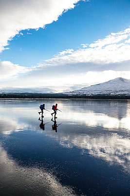 Two people moving on ice - p312m1113936f by Henrik Trygg