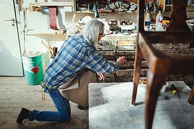 Full length of senior female craftsperson working at workshop - p426m1543018 by Maskot