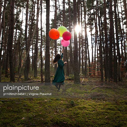 Frau mit Luftballons im Wald - p1105m2134541 von Virginie Plauchut