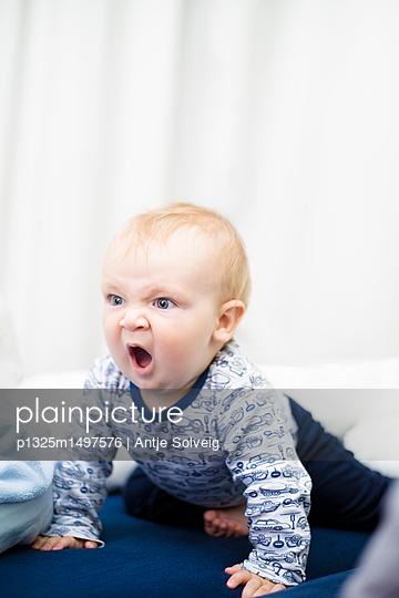 9 Monate altes Baby brüllt beim Krabbeln - p1325m1497576 von Antje Solveig