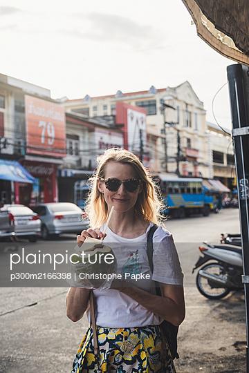 Thailand, Phuket, Old Town Phuket, europäische Frau auf Straße trinkt aus Kokusnuss - p300m2166398 von Christophe Papke