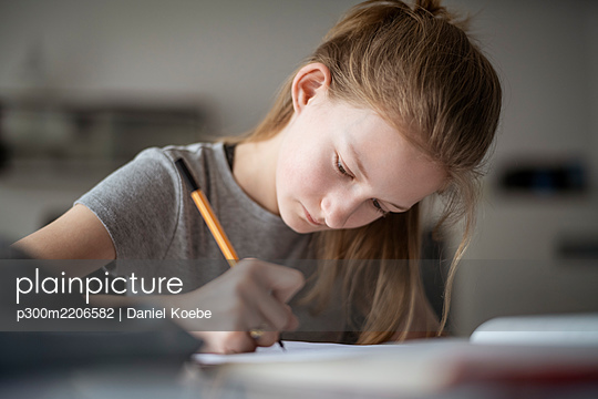 Girl learning at home, writing in exercise book - p300m2206582 by Daniel Koebe
