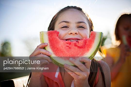 Smiling girl eating watermelon - p429m768852f by Jamie Kingham