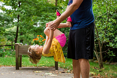 Midsection of playful father carrying cute daughter while standing against trees in yard - p1166m2068067 by Cavan Images