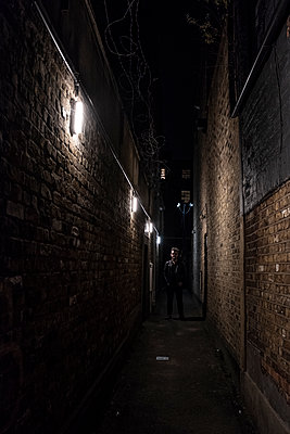 Man in narrow street at night - p1291m2026949 by Marcus Bastel