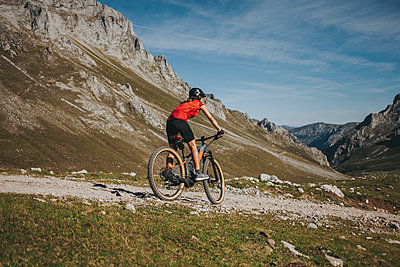 Female cyclist riding mountain bike at Picos de Europa National Park, Cantabria, Spain - p300m2240189 by David Molina Grande