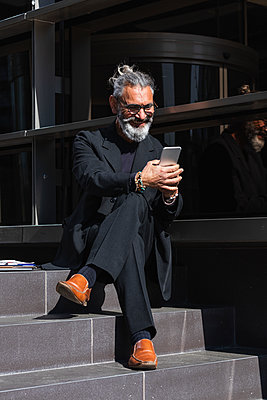 Smiling male professional using mobile phone while sitting on steps by building - p300m2276294 by NOVELLIMAGE