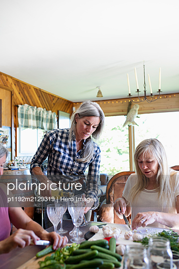 Women preparing food and pouring wine in kitchen - p1192m2129319 by Hero Images