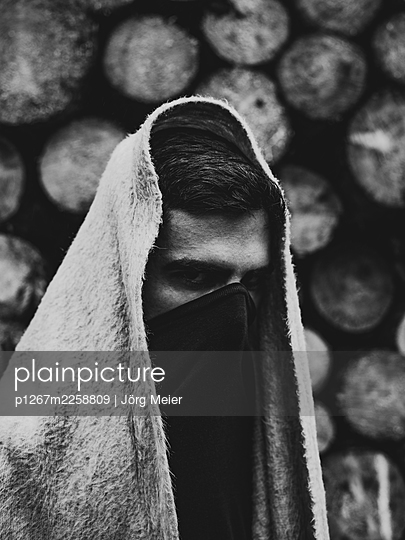Man with woollen blanket over head and shoulder hiding his face - p1267m2258809 by Jörg Meier