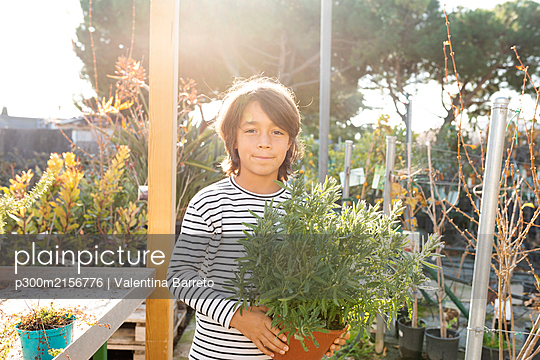 Portrait of boy with potted plant at plant nursery - p300m2156776 by Valentina Barreto