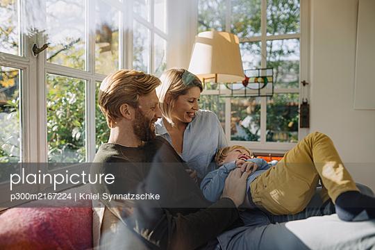Happy family having fun in sunroom at home - p300m2167224 von Kniel Synnatzschke