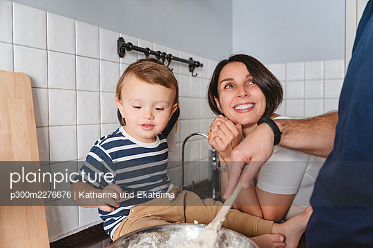 Excited mother with son looking at husband preparing food in kitchen at home - p300m2276676 by Katharina und Ekaterina