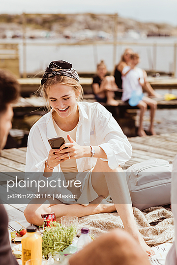 Smiling woman using smart phone sitting by friend on jetty during picnic - p426m2238118 by Maskot