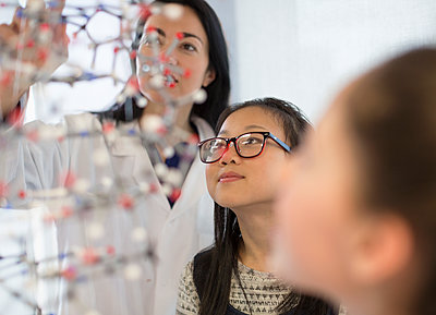 Female teacher and curious girl students examining molecular structure in laboratory classroom - p1023m2187370 by Martin Barraud