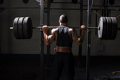 An athlete prepares to do back squats. - p1166m2094516 by Cavan Images