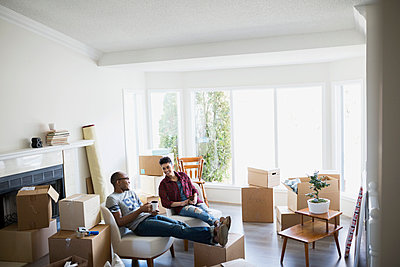 Couple surrounded by moving boxes relaxing with coffee - p1192m1019813f by Hero Images