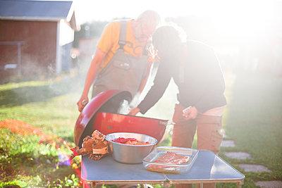 Couple having grill in garden - p312m2161942 by Matilda Holmqvist