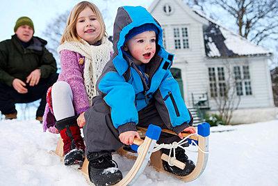 Scandinavian children on a sled - p4296019f by Peter Hundert Photography