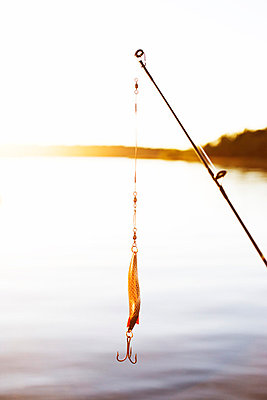Fishing tackle hanging on fishing rod - p528m713735 by Elliot Elliot
