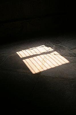 Licht fällt durch ein vergittertes Fenster - p596m1222192 von Ariane Galateau