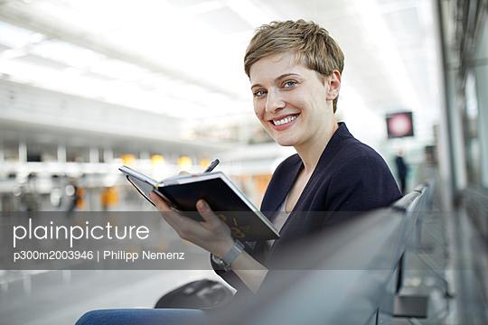 Portrait of blond woman writing in notebook - p300m2003946 von Philipp Nemenz