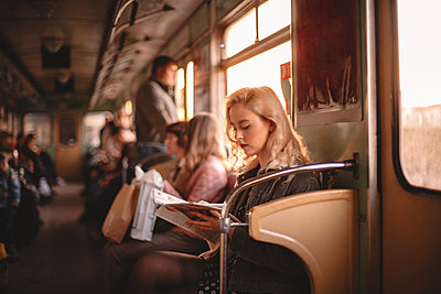 Young woman reading magazine while traveling in subway train - p1166m2153511 by Cavan Images