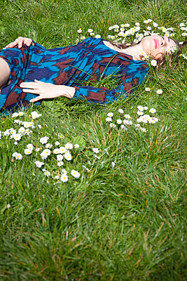 Woman Lying on Grass with Daisies  - p1248m2087687 by miguel sobreira