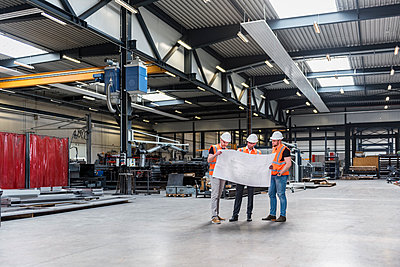 Three men wearing hard hats and safety vests looking at plan on factory shop floor - p300m1567890 von Daniel Ingold
