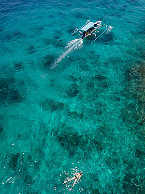 Indonesia, Bali, Aerial view of Blue Lagoon, snorkeler and banca boat - p300m2042587 by Konstantin Trubavin