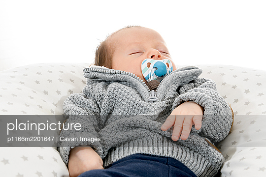 Newborn baby asleep with a pacifier - p1166m2201647 by Cavan Images