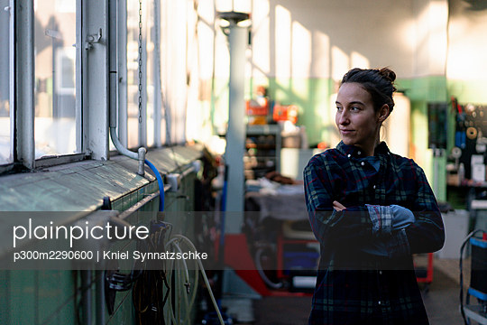 Female mechanic with arms crossed standing at workshop - p300m2290600 by Kniel Synnatzschke
