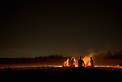 Friends sitting around bonfire at beach during night - p1166m1096304f by Cavan Images