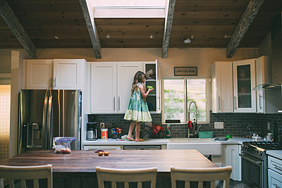 Side view of girl standing on kitchen counter - p1166m1473617 by Cavan Images