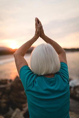 Senior woman doing yoga on seaside rocks during sunset - p1315m1518240 by Wavebreak