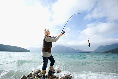 Germany, Bavaria, Walchsensee, Senior woman fishing in lake - p3007279f by Westend61