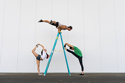 Three acrobats doing tricks on a ladder - p300m2012347 by VITTA GALLERY
