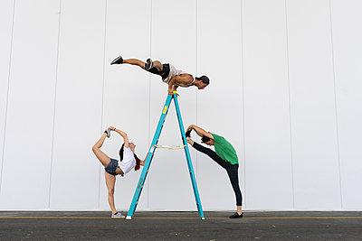 Three acrobats doing tricks on a ladder - p300m2012347 von VITTA GALLERY