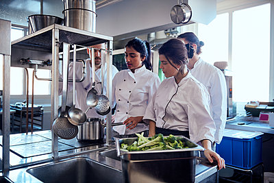 Chef team looking at colleague cooking food in commercial kitchen - p426m2016928 by Maskot
