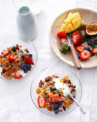 Bowls of apricot granola with fruit - p42919178 by Brett Stevens