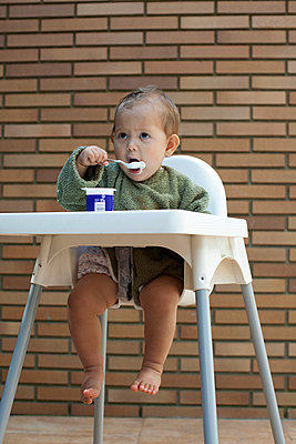 Baby girl sitting in high chair, eating yogurt with spoon - p623m699668f by Antoine Arraou
